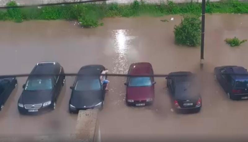После сильного ливня автовладельцу пришлось залезать в машину через окно (ВИДЕО)